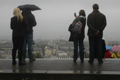 People capturing the view of Paris from the Montmartre on a rainy morning.